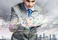 Young man in Business suit with magnifying glass looking over a city