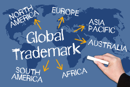 Global Trademark - blue chalkboard with female hand and text and world map in the background